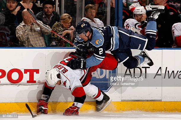 Keith Ballard of the Florida Panthers collides with Tim Gleason of the Carolina Hurricanes at the BankAtlantic Center on March 6 2010 in Sunrise...