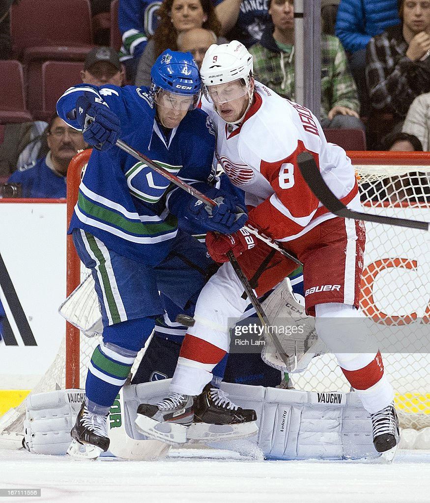 Keith Ballard #4 of the Vancouver Canucks and Justin Abdelkader #8 of the Detroit Red Wings battle for position in front of goalie Cory Schneider #35 of the Vancouver Canucks as a puck is shot towards the net during the second period in NHL action on April 20, 2013 at Rogers Arena in Vancouver, British Columbia, Canada.
