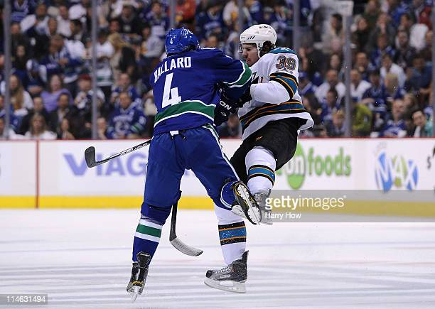 Keith Ballard of the Vancouver Canucks checks Logan Couture of the San Jose Sharks in the open ice in Game Five of the Western Conference Finals...
