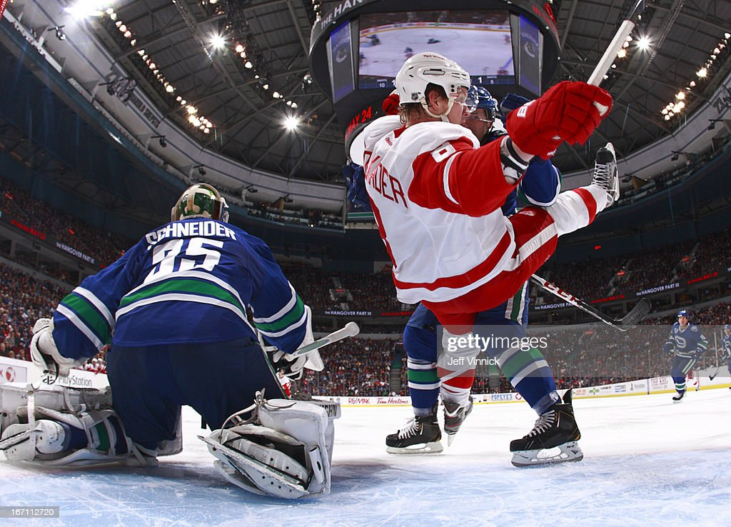Keith Ballard #4 of the Vancouver Canucks pushes Justin Abdelkader #8 of the Detroit Red Wings into the net beside Cory Schneider #35 of the Canucks during their NHL game at Rogers Arena April 20, 2013 in Vancouver, British Columbia, Canada. Vancouver won 2-1.