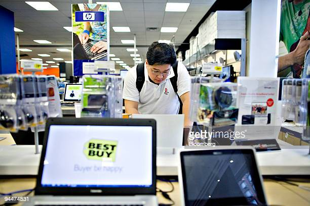 Keith Chan looks over an Eee PC netbook at a Best Buy store in New York US on Tuesday Dec 15 2009 Best Buy Co the largest electronics retailer said...