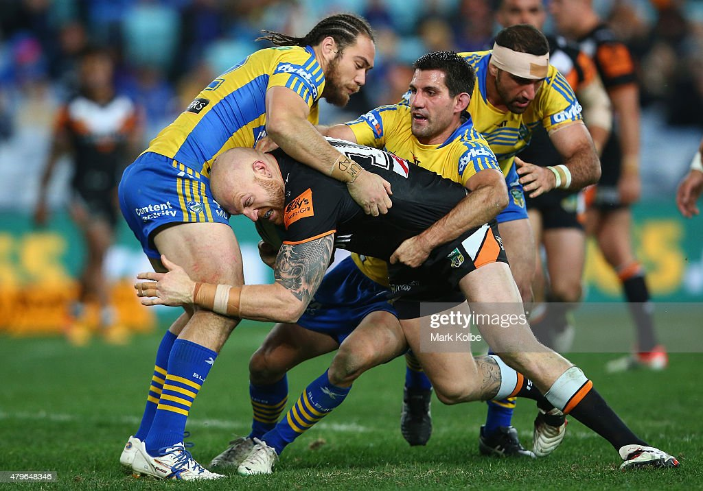 Keith Galloway of the Wests Tigers is tackled by Tepai Moeroa and Isaac De Gois of the Eels during the round 17 NRL match between the Wests Tigers and the Parramatta Eels at ANZ Stadium on July 6, 2015 in Sydney, Australia.