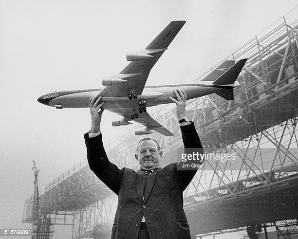 Keith Granville Managing Director of BOAC holding up a model of the Boeing 747 jet with the new aircraft hangars under construction in the background...