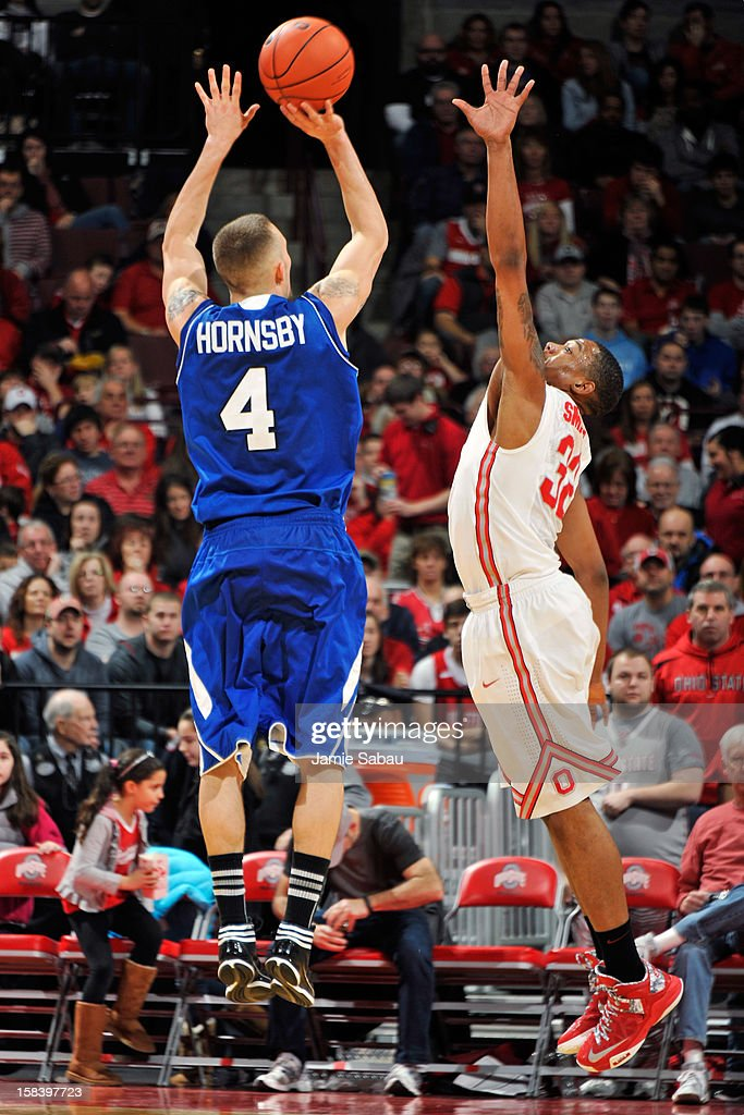 Keith Hornsby #4 of the UNC Asheville Bulldogs attempts a three-point shot over Lenzelle Smith, Jr. #32 of the Ohio State Buckeyes in the second half on December 15, 2012 at Value City Arena in Columbus, Ohio. Hornsby led all scorers with 26 points in the 90-72 loss to the Buckeyes.