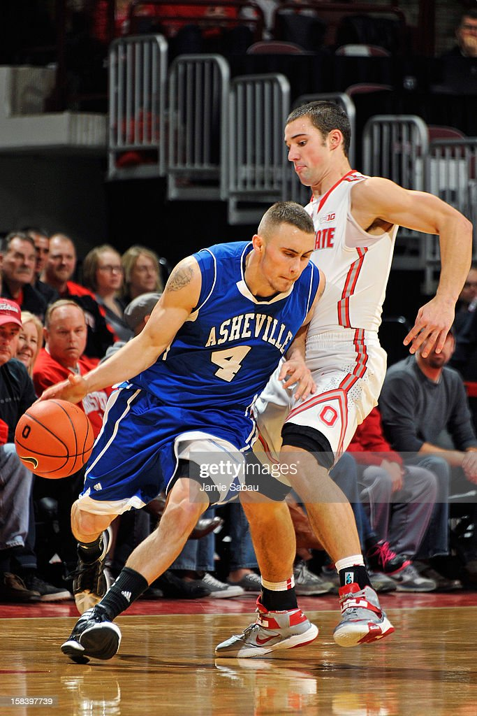 Keith Hornsby #4 of the UNC Asheville Bulldogs dribbles around Aaron Craft #4 of the Ohio State Buckeyes in the first half on December 15, 2012 at Value City Arena in Columbus, Ohio. Ohio State defeated UNC Asheville 90-72.