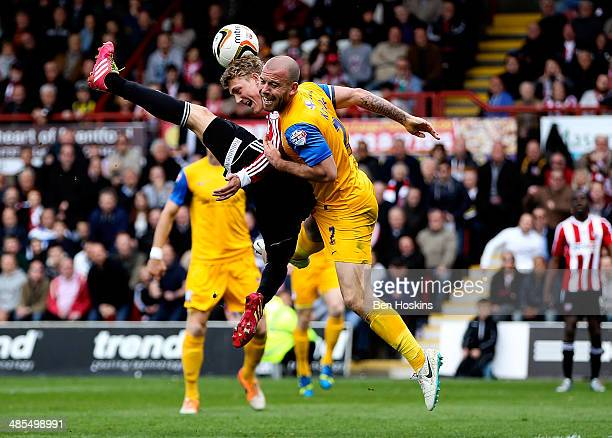 Keith Keane of Preston challenges George Saville of Brentford in the air during the Sky Bet League One match between Brentford and Preston North End...