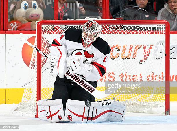 Keith Kinkaid of the New Jersey Devils deflects a Carolina Hurricanes shot during a NHL game at PNC Arena on December 3 2015 in Raleigh North Carolina