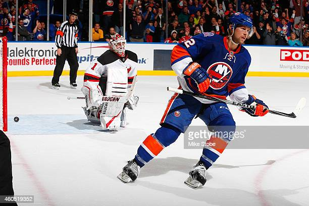 Keith Kinkaid of the New Jersey Devils looks on as Josh Bailey of the New York Islanders reacts after scoring the shootout game winning goal at...