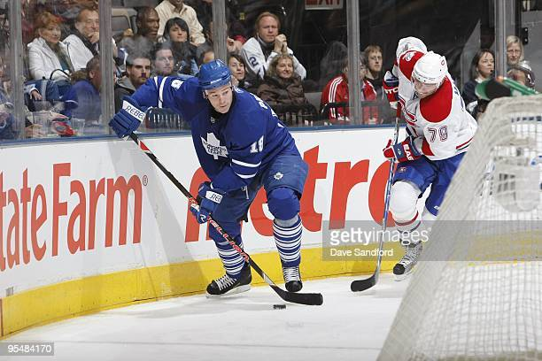 Keith Primeau of the Toronto Maple Leafs plays the puck along the boards away from Andre Markov of the Montreal Canadiens during their NHL game at...