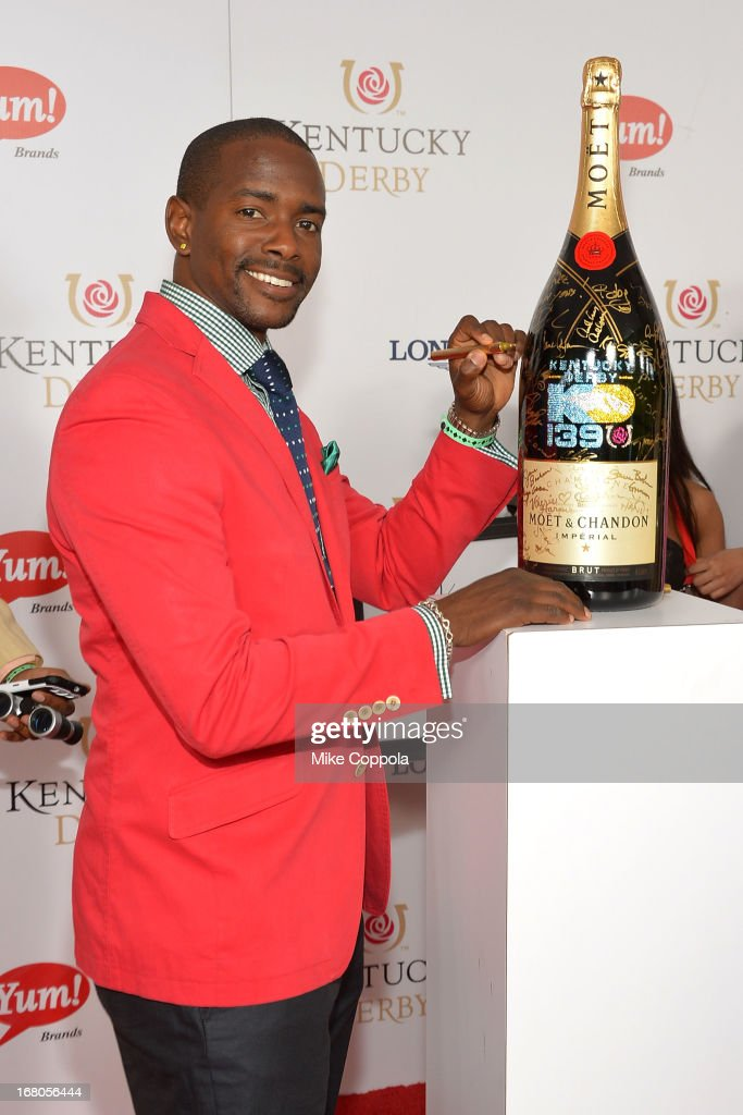 Keith Robinson signs the Moet & Chandon 6L for the Churchill Downs Foundation during the 139th Kentucky Derby at Churchill Downs on May 4, 2013 in Louisville, Kentucky.