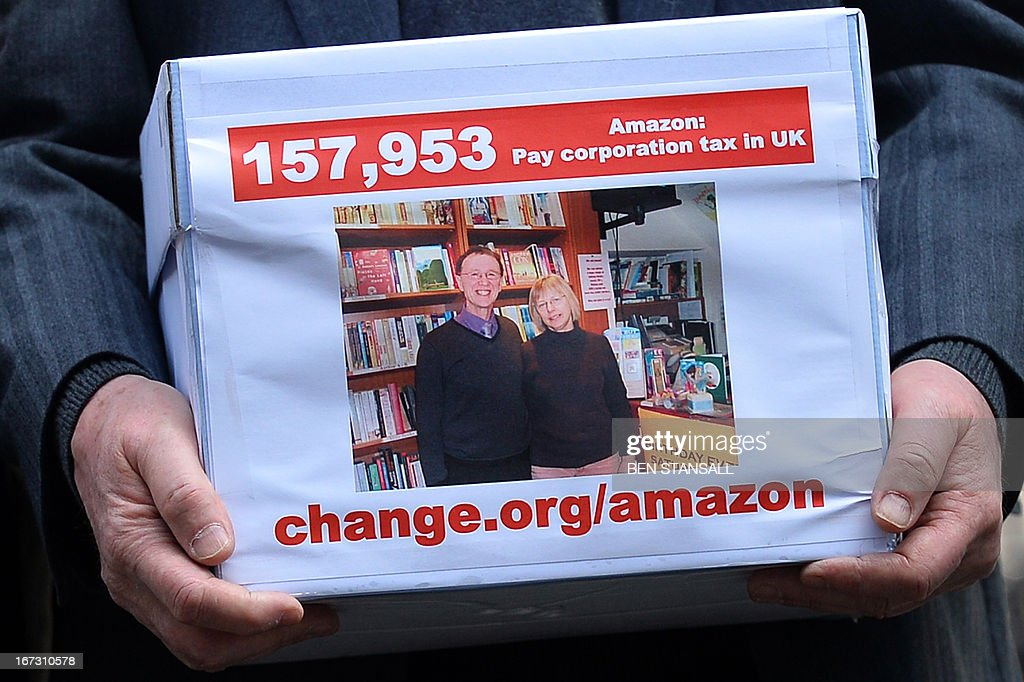Keith Smith who runs bookshops in Warwick and Kenilworth in Warwickshire with his wife Frances holds a box containing a petition signed by more than...