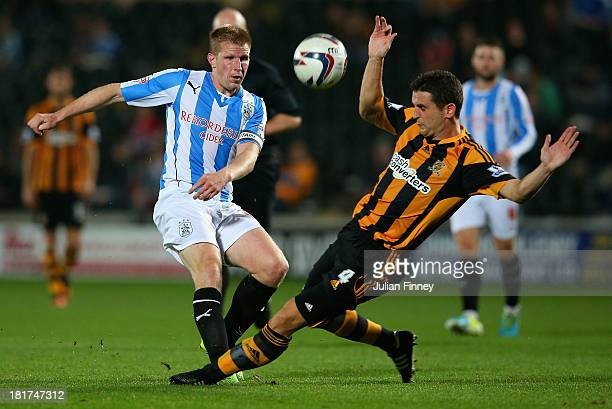 Keith Southern of Huddersfield Town shoots as Alex Bruce of Hull City tries to block during the Capital One Cup third round match between Hull City...