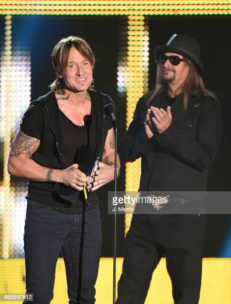 Keith Urban accepts an award from Kid Rock onstage during the 2017 CMT Music Awards at the Music City Center on June 7 2017 in Nashville Tennessee