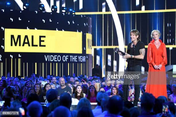 Keith Urban accepts an award presented by Katherine Heigl onstage at the 2017 CMT Music Awards at the Music City Center on June 7 2017 in Nashville...