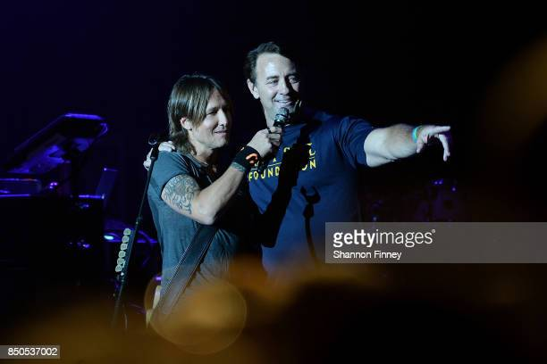 Keith Urban invites a military audience member to join him onstage at the VetsAid Charity Benefit Concert at Eagle Bank Arena on September 20 2017 in...