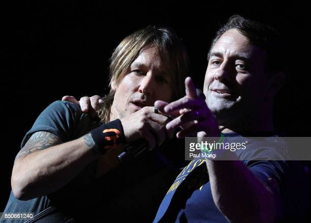 Keith Urban invites former Navy Seal John Burnham onstage during the VetsAid Charity Benefit Concert at Eagle Bank Arena on September 20 2017 in...