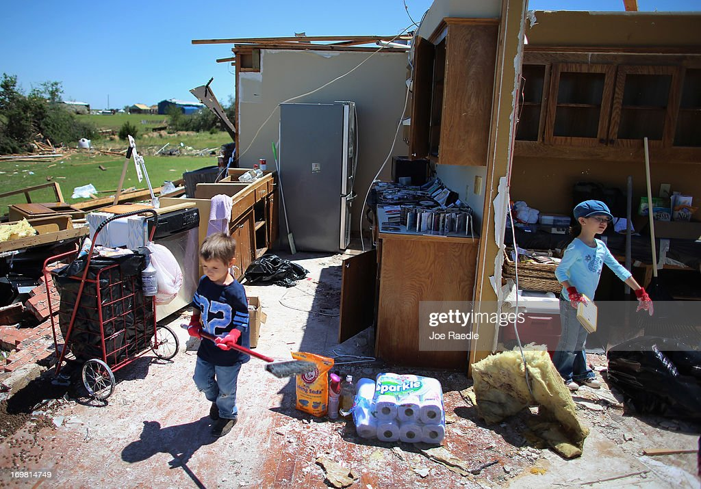 Keith Welton (L) and Infiniti Welton help salvage what they can from their grandfather's home after it was destroyed by a tornado on June 2, 2013 in El Reno, Oklahoma. The tornado ripped through the area friday killing at least 9 people, injuring many and destroying homes and buildings.