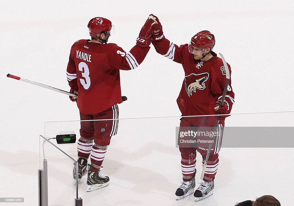 Keith Yandle and Matthew Lombardi #8 of the Phoenix Coyotes high-five after defeating the Columbus Blue Jackets in the NHL game at Jobing.com Arena on January 23, 2013 in Glendale, Arizona. The Coyotes defeated the Blue Jackets 5-1.