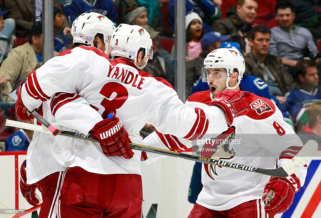 Keith Yandle and Tobias Rieder congratulate Martin Hanzal of the Arizona Coyotes who scored against the Vancouver Canucks during their NHL game at...