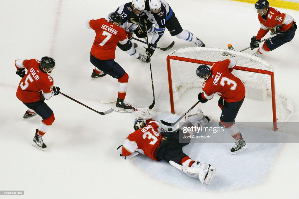 Keith Yandle #3 keeps the puck from crossing the goal line as Goaltender James Reimer #34 of the Florida Panthers is sprawled on the ice during third period action against the Winnipeg Jets at the BB&T Center on December 7, 2017 in Sunrise, Florida. The Panthers defeated the Jets 6-4.
