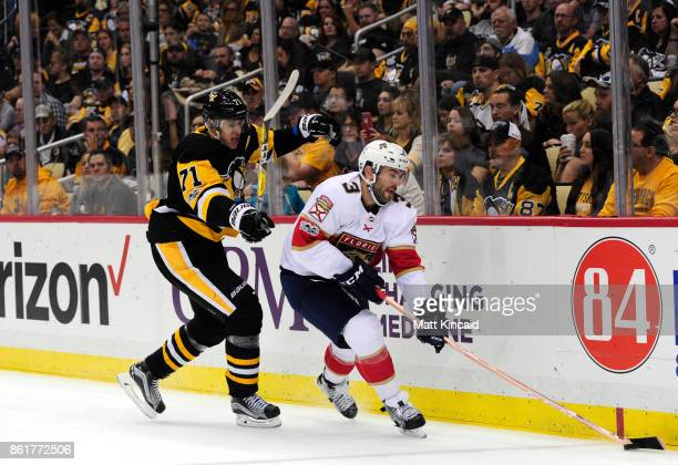 Keith Yandle of the Florida Panthers skates with the puck against Evgeni Malkin of the Pittsburgh Penguins at PPG PAINTS Arena on October 14 2017 in...