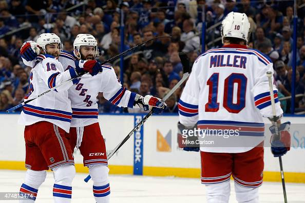 Keith Yandle of the New York Rangers celebrates with teammate Derick Brassard and JT Miller after the second goal against Ben Bishop of the Tampa Bay...