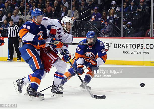 Keith Yandle of the New York Rangers gets the shot off as he is checked by Calvin de Haan and Johnny Boychuk of the New York Islanders during the...