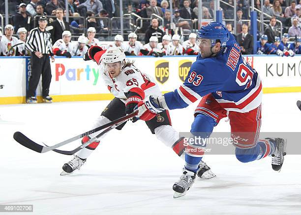 Keith Yandle of the New York Rangers shoots the puck against Erik Karlsson of the Ottawa Senators at Madison Square Garden on April 9 2015 in New...