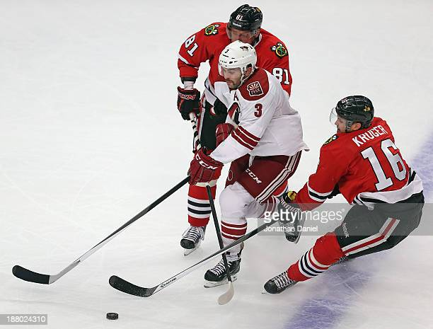 Keith Yandle of the Phoenix Coyotes skates between Marian Hossa and Marcus Kruger of the Chicago Blackhawks at the United Center on November 14 2013...