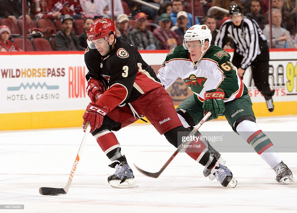 Keith Yandle #3 of the Phoenix Coyotes skates the puck up ice past Charlie Coyle #62 of the Minnesota Wild during the first period at Jobing.com Arena on February 4, 2013 in Glendale, Arizona.