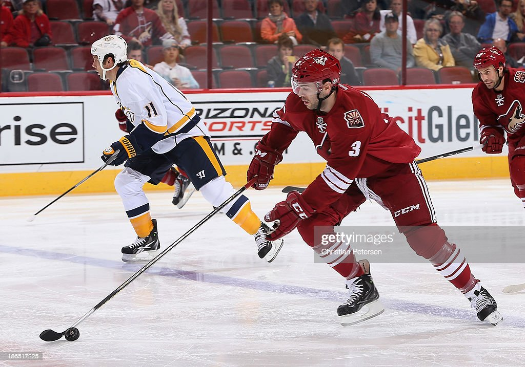 <a gi-track='captionPersonalityLinkClicked' href=/galleries/search?phrase=Keith+Yandle&family=editorial&specificpeople=606912 ng-click='$event.stopPropagation()'>Keith Yandle</a> #3 of the Phoenix Coyotes skates with the puck ahead of <a gi-track='captionPersonalityLinkClicked' href=/galleries/search?phrase=David+Legwand&family=editorial&specificpeople=202553 ng-click='$event.stopPropagation()'>David Legwand</a> #11 of the Nashville Predators during the NHL game at Jobing.com Arena on October 31, 2013 in Glendale, Arizona. The Coyotes defeated the Predators 5-4 in an overtime shoot out.