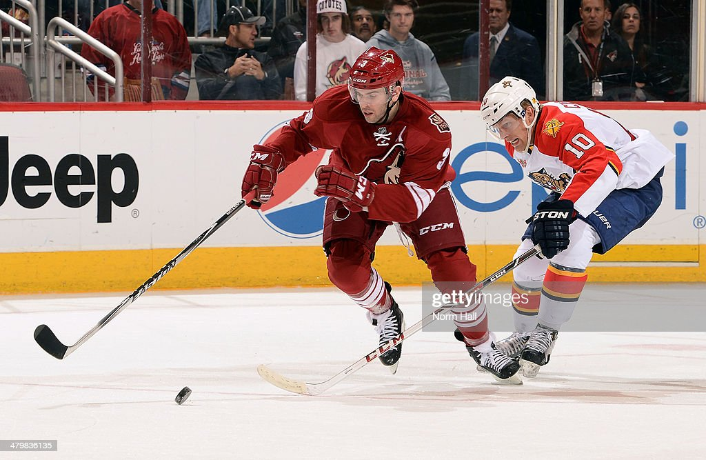 Keith Yandle of the Phoenix Coyotes skates with the puck ahead of Joey Crabb of the Florida Panthers during the third period at Jobingcom Arena on...