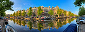 Beautiful 180 degree panoramic panorama of the UNESCO world heritage Keizersgracht canal  in Amsterdam, the Netherlands, on a sunny summer day with a blue sky and mirror reflection