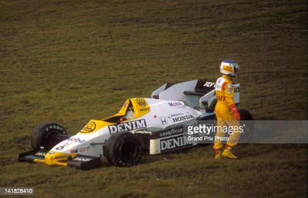 Keke Rosberg of Finland walks away from the Williams Grand Prix Engineering Williams FW09B Honda V6 turbo after a first corner crash after the start...