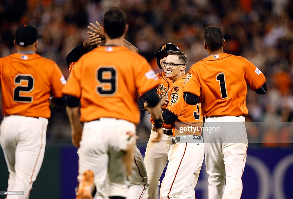 Kelby Tomlinson #37 of the San Francisco Giants is congratulated by teammates after he had the game-winning hit in the bottom of the ninth inning that scored Brandon Belt #9 against the St. Louis Cardinals at AT&T Park on August 28, 2015 in San Francisco, California.