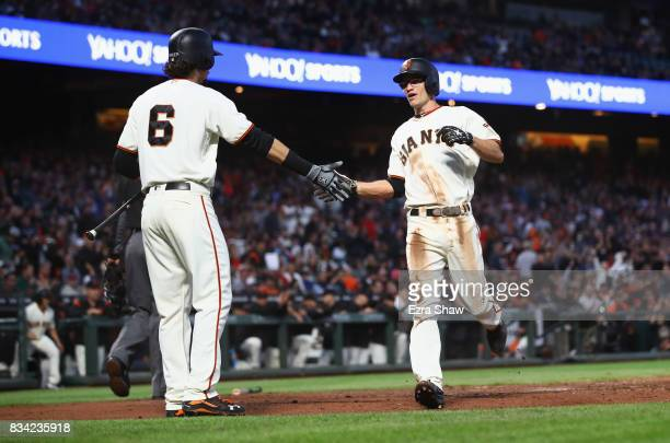 Kelby Tomlinson of the San Francisco Giants is congratulated by Jarrett Parker after he scored in the third inning against the Philadelphia Phillies...