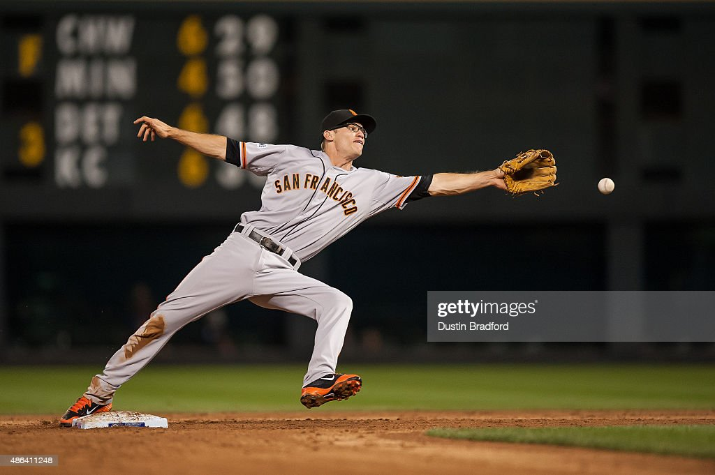 Kelby Tomlinson of the San Francisco Giants leans to field a ball on a potential double play but misses on an error by the fielder in the fourth...