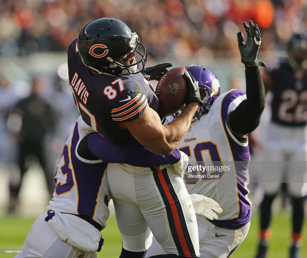 Kellen Davis #87 of the Chicago Bears catches a pass under pressure from Jamarca Sanford #33 and Eric Henderson #50 of the Minnesota Vikings at Soldier Field on November 25, 2012 in Chicago, Illinois. The Bears defeated the Vikings 28-10.