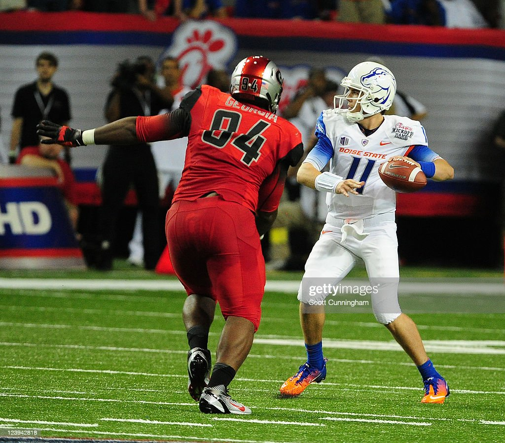 Kellen Moore of the Boise State Broncos passes as he is pressured by DeAngelo Tyson of the Georgia Bulldogs during the ChickFilA Kickoff Game at the...