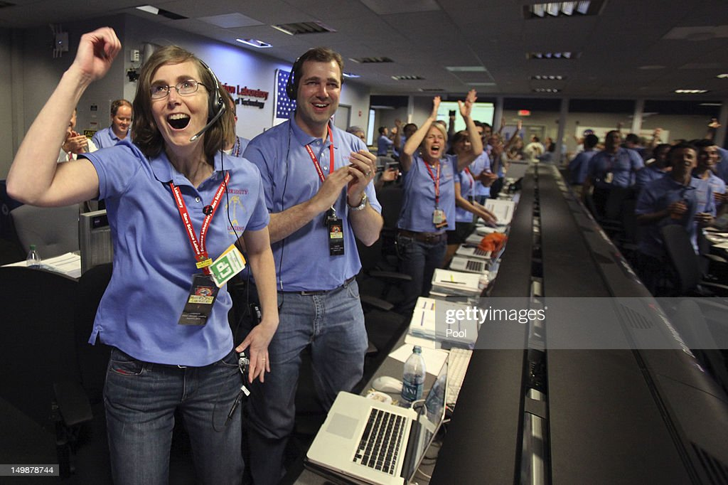 Kelley Clarke, left, celebrates as the first pictures appear on screen after a successful landing inside the Spaceflight Operations Facility for NASA's Mars Science Laboratory Curiosity rover at Jet Propulsion Laboratory on August 5, 2012 in Pasadena, California. The MSL Rover named Curiosity is equipped with a nuclear-powered lab capable of vaporizing rocks and ingesting soil, measuring habitability, and whether Mars ever had an environment able to support small life forms called microbe.