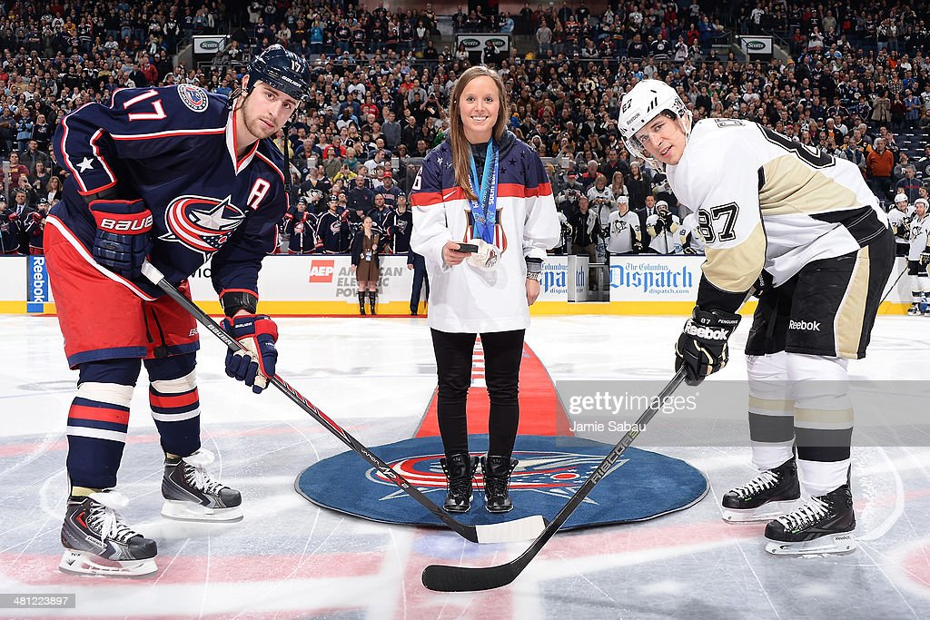 <a gi-track='captionPersonalityLinkClicked' href=/galleries/search?phrase=Kelli+Stack&family=editorial&specificpeople=6214354 ng-click='$event.stopPropagation()'>Kelli Stack</a> of the USA Olympic Women's Hockey Team drops the puck for <a gi-track='captionPersonalityLinkClicked' href=/galleries/search?phrase=Brandon+Dubinsky&family=editorial&specificpeople=2271907 ng-click='$event.stopPropagation()'>Brandon Dubinsky</a> #17 of the Columbus Blue Jackets and <a gi-track='captionPersonalityLinkClicked' href=/galleries/search?phrase=Sidney+Crosby&family=editorial&specificpeople=212781 ng-click='$event.stopPropagation()'>Sidney Crosby</a> #87 of the Pittsburgh Penguins on March 28, 2014 at Nationwide Arena in Columbus, Ohio.