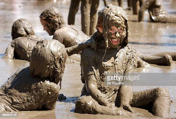 Kelli Yokom of Redford Michigan and her friend Stephanie Janssen also of Redford play with hundreds of other children in a giant lake of mud at the...