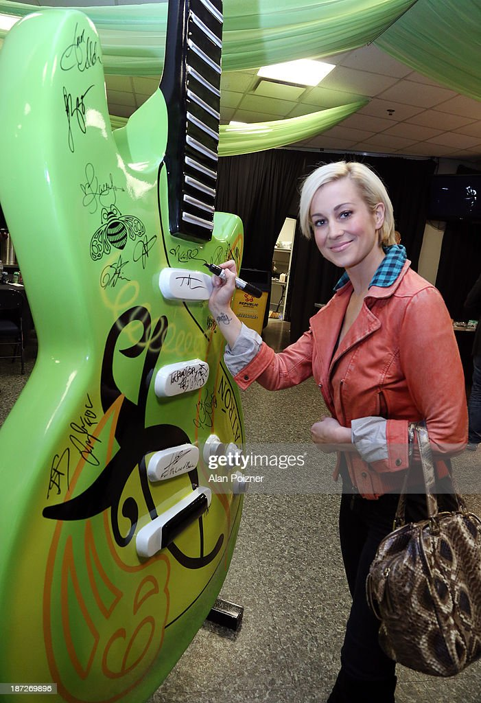 Kellie Pickler signs a giant Patron tequila guitar backstage at the CMA Awards to benefit the 'Keep the Music Playing' music education on November 3, 2013 in Nashville, Tennessee.