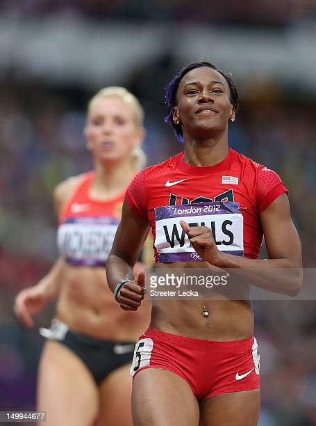 Kellie Wells of the United States reacts ahead of Cindy Roleder of Germany after competing in the Women's 100m Hurdles Semifinals on Day 11 of the...