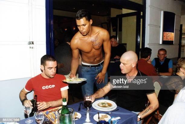 Kellner mit freiem Oberkörper serviert vor dem Restaurant 'LukiLuki' in der Motzstrasse