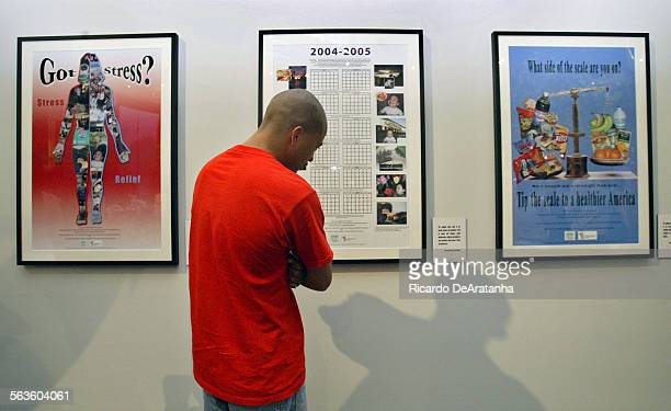 Kelly Anderson of the Watts Labor Community Action Committee looking at the photography posters depicting health concerns created by 13 Los Angeles...
