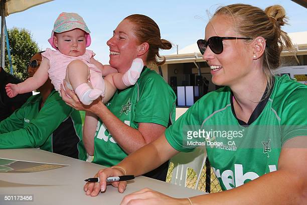Kelly Applebee of the Stars plays with her daughter Ella next to Meg Lanning during a signing session at Casey Fields on December 13 2015 in...