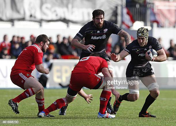 Kelly Brown of Saracens attempts to hand off CJ Stander of Munster during the European Rugby Champions Cup pool one match between Saracens and...