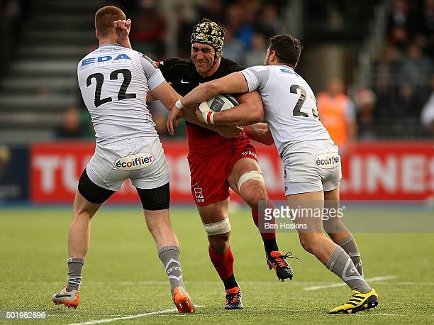 Kelly Brown of Saracens is tackled by Rory Clegg and Vincent Martin of Oyonnax during the European Rugby Champions Cup match between Saracens and...