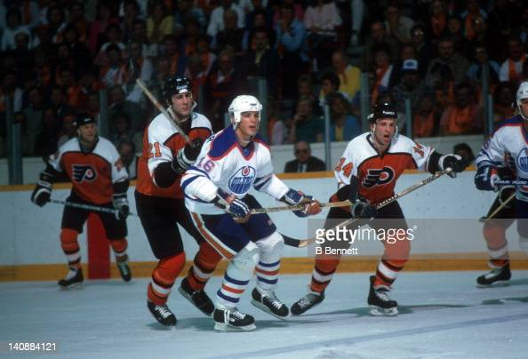 Kelly Buchberger of the Edmonton Oilers skates on the ice as he is defended by Dave Brown and Ron Sutter of the Philadelphia Flyers during Game 1 of...